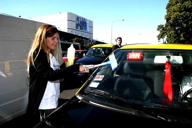 los artistas se dieron cita en la esquina de Tagle y Figueroa Alcorta para limpiar los parabrisas de los autos que se detenían en el semáforo del lugar –una de las modalidades de trabajo infantil más comunes-, sorprendiendo a los transeúntes e informándolos sobre las causas y consecuencias del trabajo infantil. En la foto; Dalma Maradona