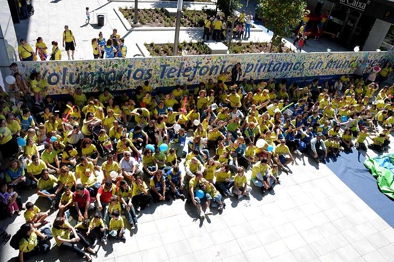 Un grupo de asistentes al evento, al pie del mural, símbolo de su compromiso con la solidaridad