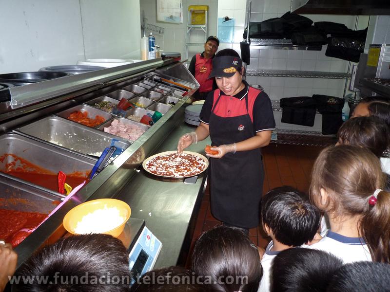 Los niños aprendiendo como se elabora una pizza.