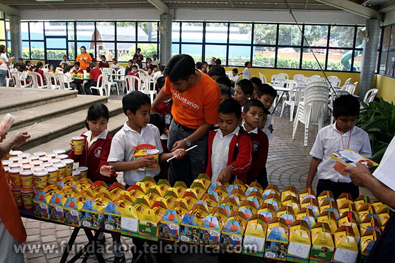 Los niños recibiendo su merienda para reponer energías.