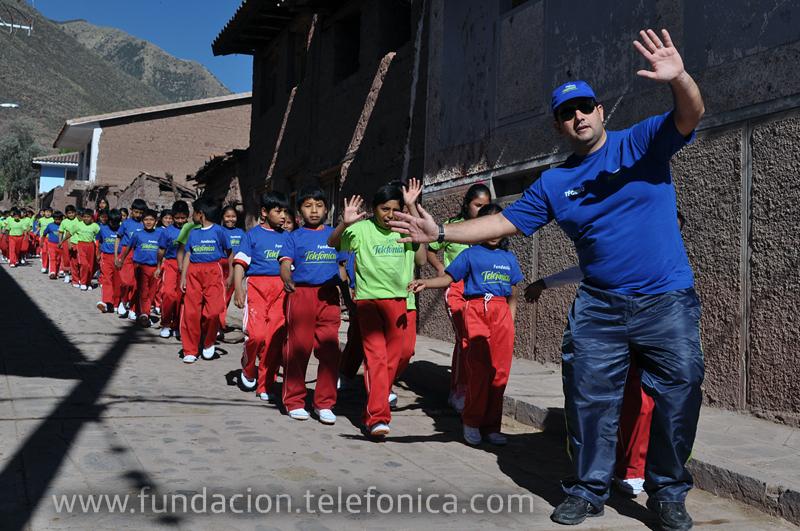 Eduardo Acuña, coordinador del programa de Academias Deportivas Escolares Fundación Telefónica en la especialidad de atletismo, junto con alumnos de la red rural Fe y Alegría 44 de Andahuaylillas.