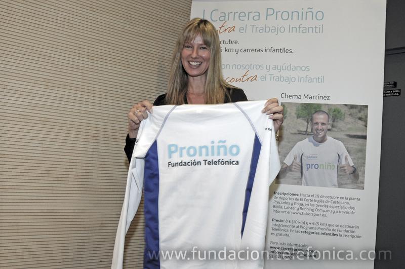 La presentadora de televisión Anne Igartiburu mostrando la camiseta Proniño para la carrera.