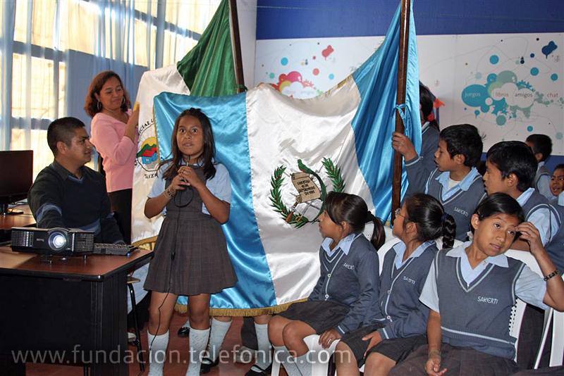 Los niños de Guatemala presentan su bandera de país y colegio.
