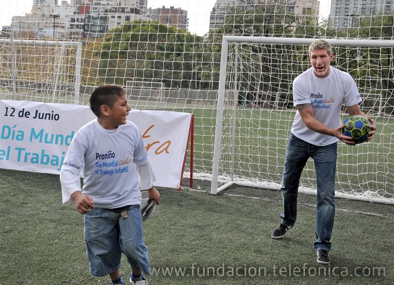 El futbolista Martín Palermo jugando con un beneficiario del programa Proniño.