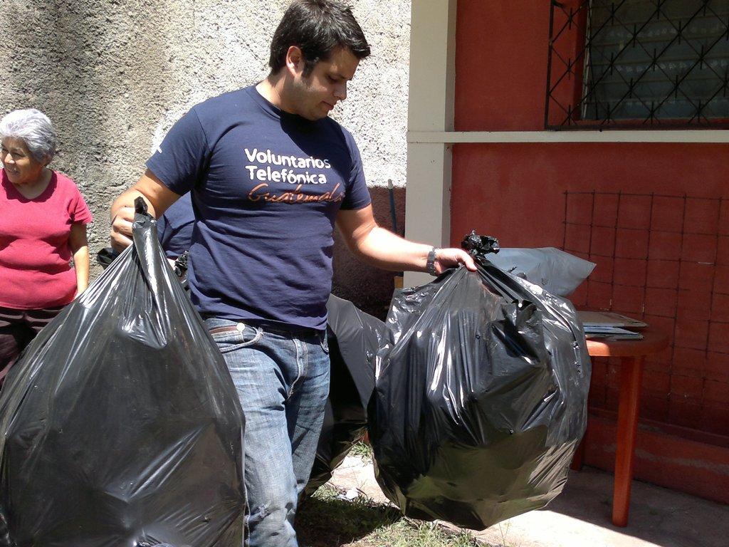 Bolsas con las botellas plásticas son trasladadas al interior de la casa.