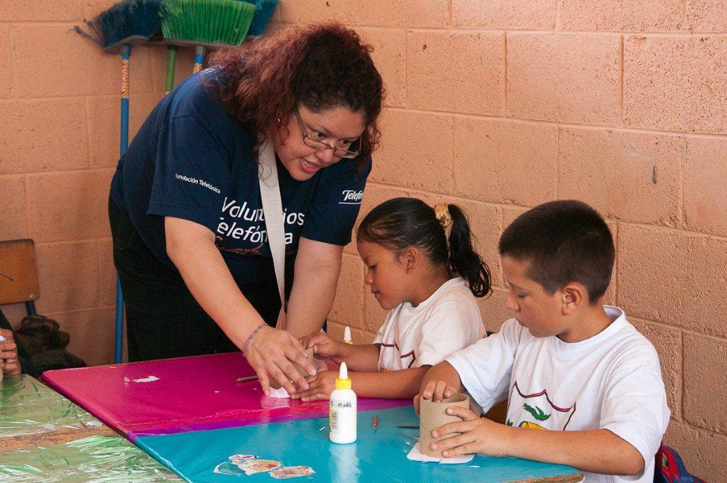 Los Voluntarios Telefónica ayudan a los niños en su trabajo manual.